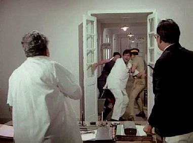 Dewan and a constable drag Roy off