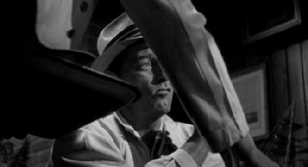 A frame from Cape Fear: a waiter's arm, and Robert Mitchum
