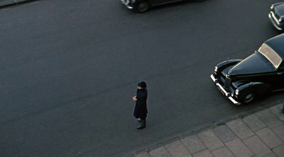 A man in a black coat appears to be trailing Kit...