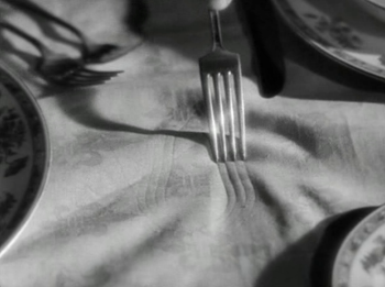 Constance 'draws' on the tablecloth with her fork