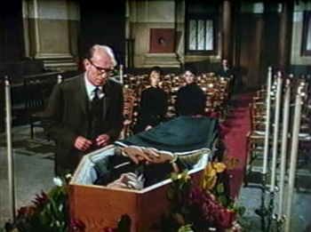 A visitor comes up to Charles's coffin