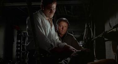 Renaud examines Gabriel's leg while Moran looks on