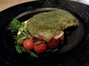 Herb crusted fish on a bed of sweet button onions, diced potatoes, and cherry tomatoes.
