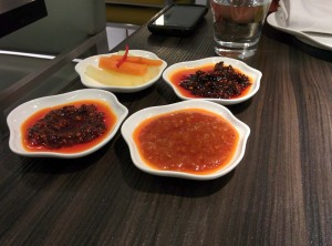 A selection of sauces, with pickled vegetables.