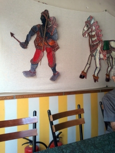 Leather puppets on a wall at Carnatic Cafe.