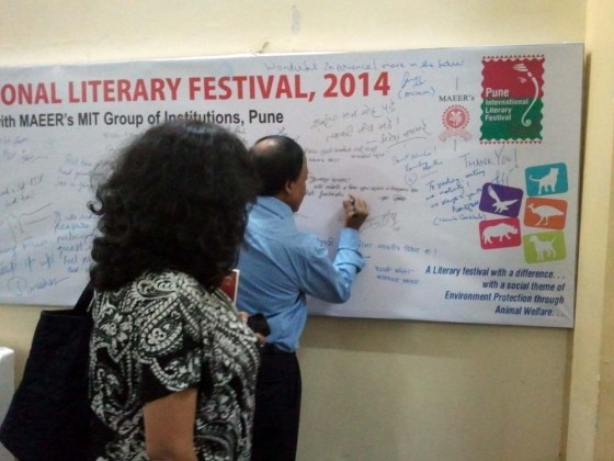 Ramesh Menon signs the authors' board while Manjiri Prabhu looks on.