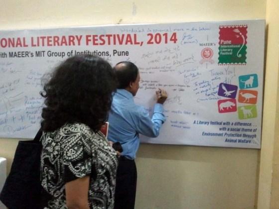 Ramesh Menon signs the authors' board while Manjiri Prabhu looks on.