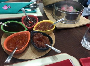 Five types of sauces at Yum Yum Cha, with pink crab dumplings in the background.