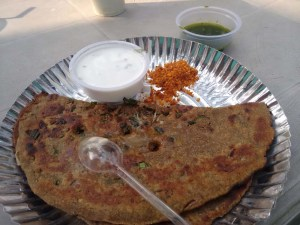 A fantastic thaalipeeth with two types of chutney and a raita.