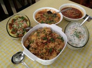 An array of goodies: chicken biryani, onion raita, mutton korma, baingan mirch ka salan, salad.